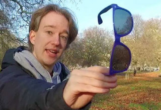 man holding sunglasses showing the pulfrich effect