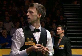 Professional billiards player is looking into the crowd after he heard a huge fart