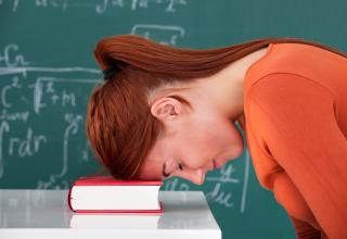 teacher in classroom rests her head on a book