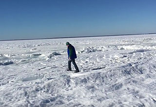 man walking on the frozen ocean off of cape cod