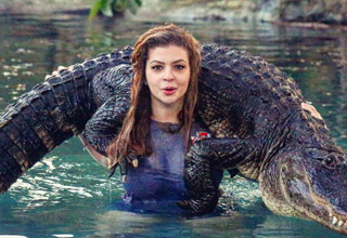 red headed woman weaing a blue top in the water holding an alligator across her shoulders