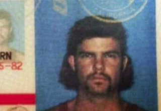 Man with a mustache and mullet in an ID photo