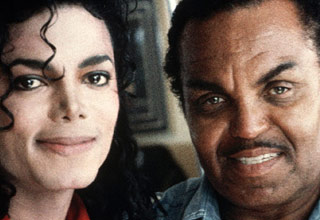 michael jackson wearing a red shirt  standing next to joe jackson wearing a blue shirt