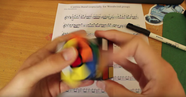 hands holding a rubik's cube and a piece of sheet music in the background