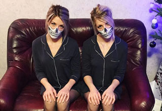two ladies on a couch wearing skull masks