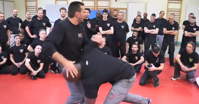 a class room full of mma students standing on a red rug wearing all black shirts and blue jeans while the instructor demonstrates moves