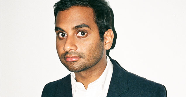 Aziz Ansari in a suit standing in front of a white wall, eyes wide open