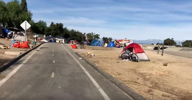 a bike path going through a homeless tent camp