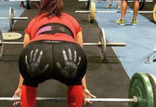 a girl at the gym lifting weights with a red shirt and black pants that have white handprints on her butt