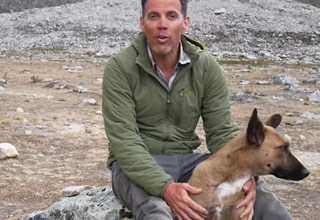 actor and personality steve-o wearing a green jacket and blue jeans,  sitting on a rock petting a dog