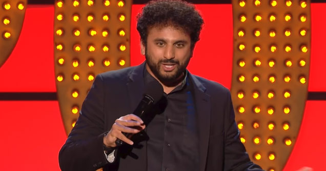 comedian nish kumar on a stage with marquee style letters doing his show