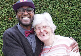 a young black man hugs an elderly white lady both are smiling it is a happy picture