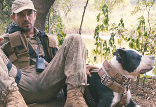 former-millitary-soldier-sitting-with-a-pitbull-wearing-leather-protective-gear-sitting-in-the-african-bush