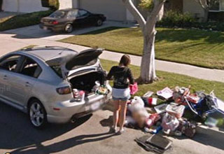 a woman who got kicked out of her home for cheating stands by her car with the trunk open and all her things on the ground