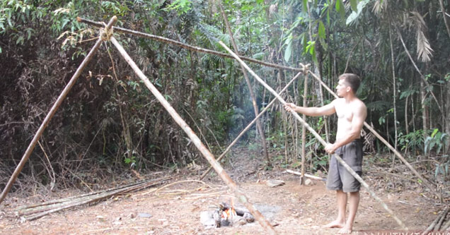 man without a shirt in the woods builds an A-frame house