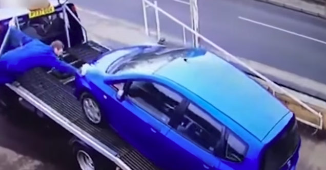 a tow truck driver wearing all blue attempts to hold onto a blue car rolling away