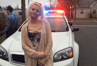 a blonde girl sitting against a white police car with its lights on while flipping us the bird