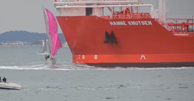 a sailboat with pink sails on choppy water is almost run over by a giant red ship