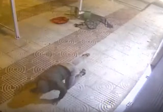 man in all black crawling on the ground after getting hit by a chair