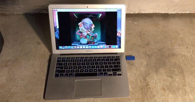 apple laptop on the floor with a blue usb drive sticking out of it