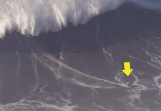 a photo of a massive wave with a man surfing and a yellow arrow pointing at him