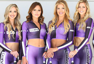 a group of attractive women wearing purple and black jumpsuits pose for the camera