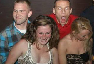 people dancing in a club and a man in a red shirt is making a funny face .
