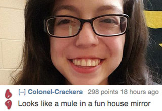 a girl with brown hair and black framed glasses smiling with a reddit comment about her apperance
