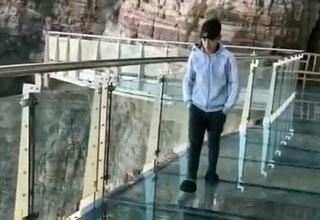 Chinese tourist walking across glass-bottom bridge getting pranked
