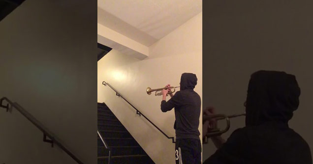 a man wearing a hoodie plays a trumpet into a stare case