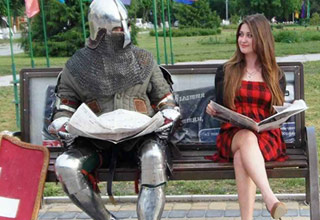a man in a knights amor and a woman in a red checkered dress holding a book and sitting on a park bench