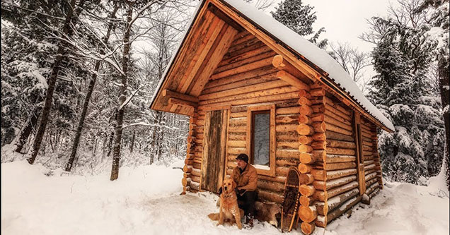 man and his dog in front of his finished cabin