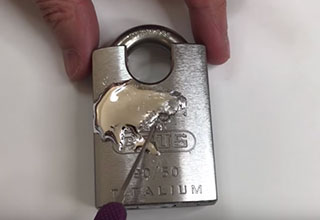 titanium padlock with gallium spread over it