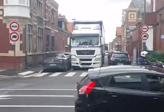 Truck and trailer driving down alley in France destroying cars during turn