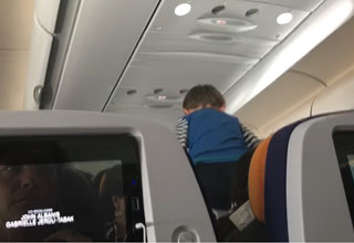 annoying kid on 8 hour flight sitting on the top of his seat screaming