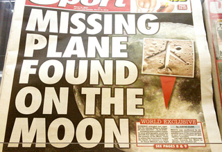 a photo of a tabloid cover saying missing plane found on moon