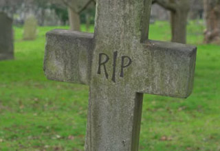 an old grave stone cross that says RIP
