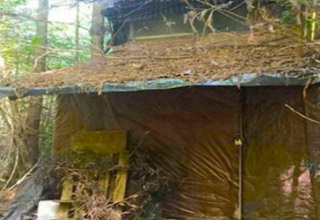 old cabin built in the woods covered in leaves and sticks found by a ranger.