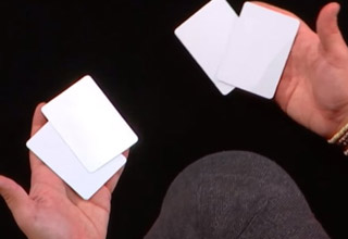 a man holding blank cards performs a magic tragic