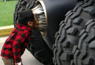 kid sticks his face into a large burner with big tires