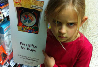a little girl holding a toy that says for boys making an angry face