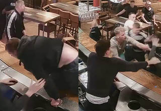 man climbing on bar, other man attempting to prevent entangled patrons from fighting