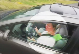 woman driving a gray car while texting