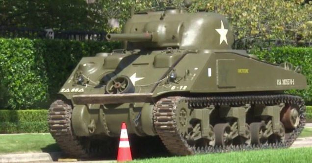 a world war two era tank with a traffic cone in front of it