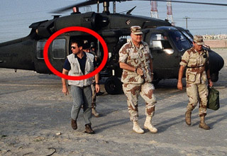 soldiers getting out of a helicopter escorted by men in plain clothes with guns