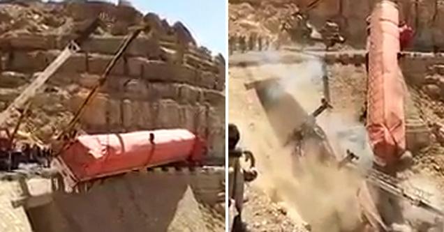 truck in peril on a bridge next to a crane in the desert