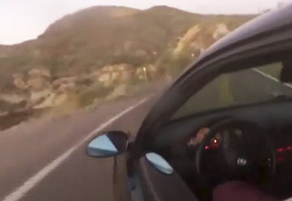 a man speeding on a winding road is about to drive off a giant cliff