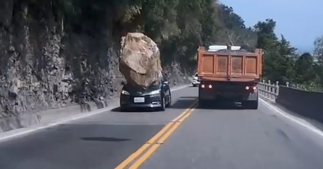 a large rock falls off a cliff and almost hits a black car driving towards it