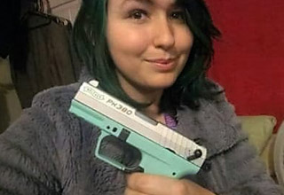 a woman with blue and green hair holding a turquoise colored pistol