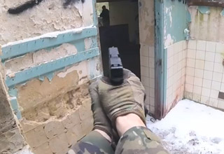 a man wearing cammo and gloves is holding a pistol while entering a building